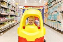 小男孩愉快在超级市场推车以在购物中心或购物中心的一辆汽车的形式 免版税库存图片