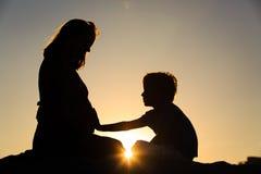 小男孩感人的怀孕的母亲肚子剪影  免版税库存照片