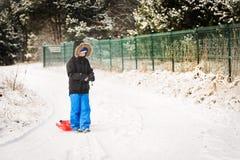 小男孩拉扯他的红色塑料雪撬 免版税库存图片