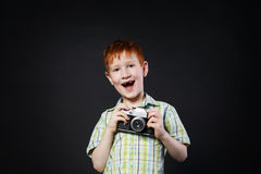 小男孩拍与葡萄酒照相机的照片在黑背景 免版税库存照片
