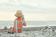 小男孩拍在巧妙的电话的照片 坐小卵石b 免版税库存图片