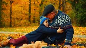 小男孩拥抱他的祖父在秋天公园坐 免版税库存图片