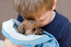 小男孩拥抱充满爱一只湿狗pomeranian小狗 图库摄影