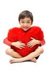 小男孩拥抱枕头心脏 免版税库存照片