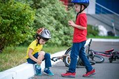 小男孩掉下他的自行车 不快乐的男孩坐asphal 免版税库存图片