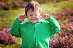 小男孩握他的在耳朵的手听不到 库存图片