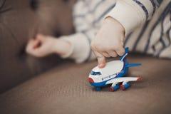 小男孩播放蓝色,红色和白色颜色玩具飞机  框架是仅男孩` s手 没有表面 关闭 库存图片