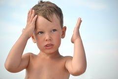 小男孩是太热的在阳光下没有帽子 孩子有头疼 孩子拿着他的头,显示那头疼 免版税库存照片