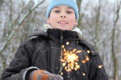 小男孩暂挂闪烁发光物在森林里 库存图片