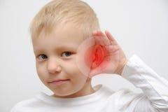 小男孩有一个病的耳朵 免版税库存图片