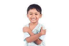 小男孩横渡了一武装和微笑 免版税库存图片