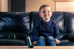 小男孩沙发的和有哮喘吸入器的 免版税图库摄影