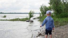 小男孩沿河走 孩子在湖附近跑 t 使用在水附近的愉快的婴孩 股票录像