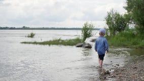 小男孩沿河走 孩子在湖附近跑 t 使用在水附近的愉快的婴孩 股票视频