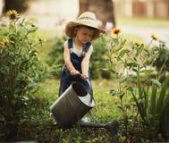 小男孩浇灌的花 库存照片