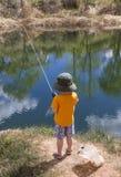 小男孩渔在池塘 免版税库存照片