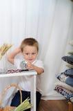 小男孩演奏桌面时钟 有土气装饰的屋子 免版税图库摄影