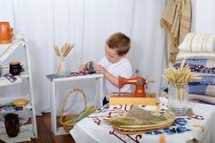 小男孩演奏桌面时钟 有土气装饰的屋子 免版税库存图片