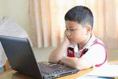 小男孩演奏笔记本。 免版税库存照片
