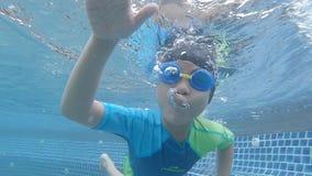 小男孩潜水和挥动的你好在水下在游泳场 股票录像