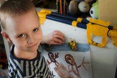 小男孩炫耀在磁性画板固定的他的图画 免版税图库摄影