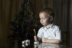 小男孩点燃在新年` s冷杉背景的蜡烛  图库摄影