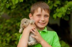 小男孩用一只兔子在手上 免版税图库摄影