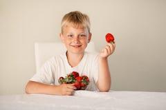 小男孩用草莓 免版税图库摄影