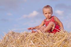 小男孩画象夏天帽子的坐一块麦田的一个干草堆 免版税图库摄影