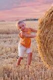 小男孩画象夏天帽子神色的在一块麦田的一个干草堆 库存图片