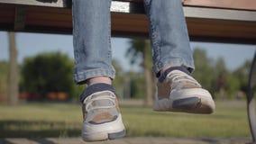 小男孩的脚坐长凳在公园 震动他的腿的孩子 单独逗人喜爱的儿童消费时间户外 股票视频