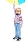 小男孩站立在一把五颜六色的伞下 库存图片
