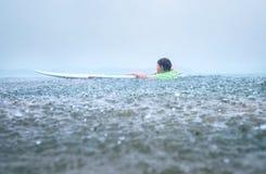 小男孩第一步在船上站起来的冲浪者尝试在trop下 免版税库存图片