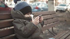 小男孩致瘾智能手机坐在城市街道的长凳 可爱宝贝有手机的男孩孩子在室外的长凳 股票录像