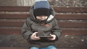 小男孩致瘾智能手机坐在城市街道的长凳 可爱宝贝有手机的男孩孩子在室外的长凳 影视素材
