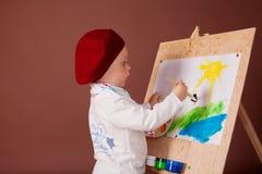 小男孩艺术家刷子和油漆绘一幅画 库存图片