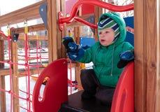 小男孩获得乐趣在冬天操场 免版税库存图片