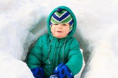 小男孩获得乐趣在冬天雪 库存照片