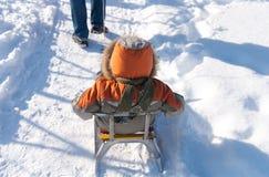 小男孩获得乐趣在雪 库存图片