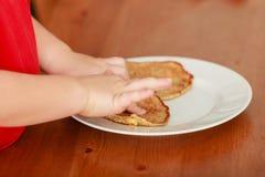 小男孩薄煎饼为breaktfast做准备 免版税库存图片