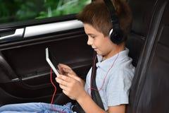小男孩观看的电影获得乐趣在汽车 免版税库存照片
