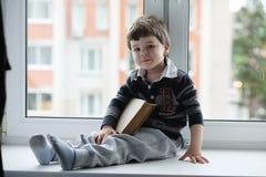小男孩读一本书 孩子坐在窗口a 库存照片