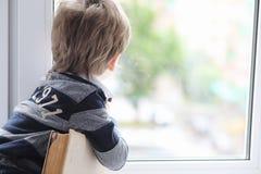 小男孩读一本书 孩子坐在窗口a 免版税图库摄影