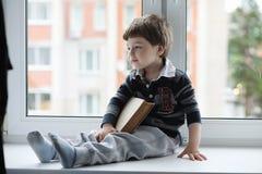 小男孩读一本书 孩子坐在窗口a 免版税库存图片