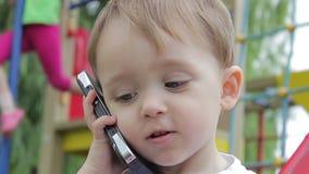 小男孩谈在电话智能手机,微笑的面孔特写镜头 股票视频