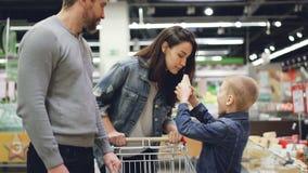 小男孩购物与他的母亲和父亲,采取从冰箱的乳酪并且嗅到然后给他的父母的它 影视素材