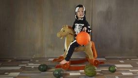 小男孩赤足在震动的玩具马的最基本的衣服 孩子愉快地庆祝万圣节,拿着pumpkin-shaped手电 股票视频