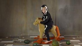 小男孩赤足在震动的玩具马的最基本的衣服 孩子愉快地庆祝万圣节,拿着pumpkin-shaped手电 影视素材