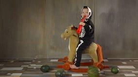 小男孩赤足在震动的玩具马的最基本的衣服 孩子愉快地庆祝万圣节,拿着pumpkin-shaped手电 股票录像