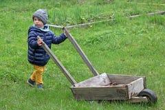 小男孩运载在草的一辆大木独轮车 孩子在国家在春天在衣服暖和 免版税库存图片